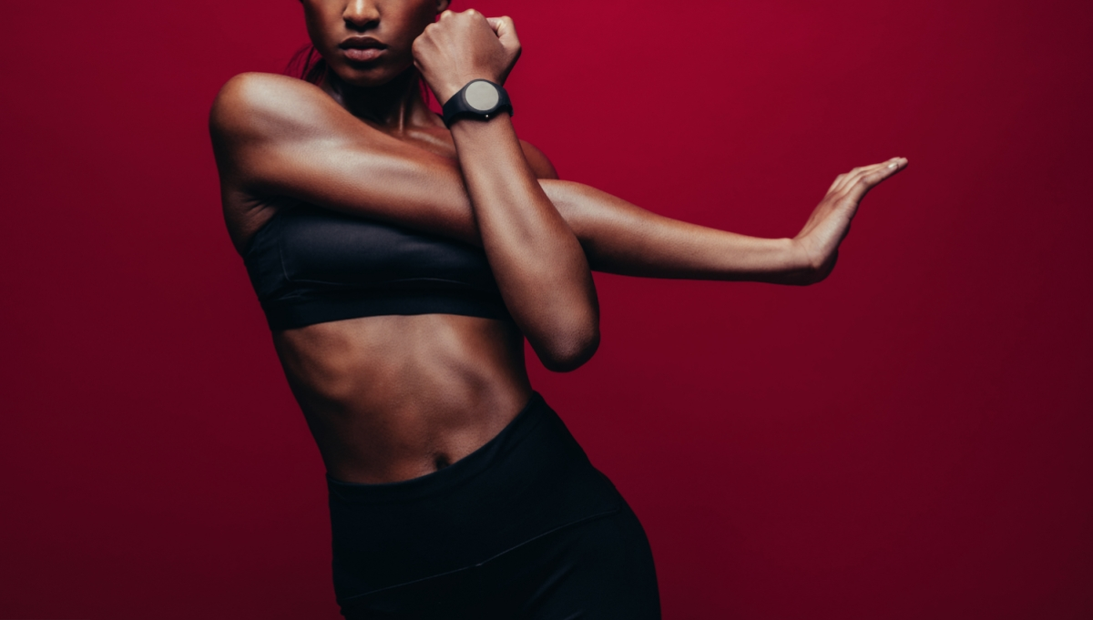 muscular woman stretching, wearing black workout gear and a watch in front of a red background