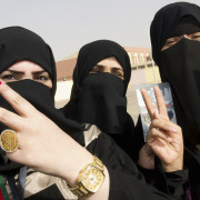 Kuwaiti girls give a victory sign as they stand in front of a polling station in Jahra
