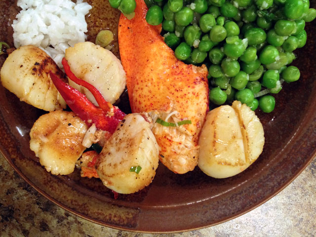 A plate of lobster pieces, scallops, rice and peas.