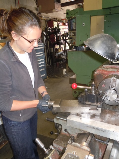 Me working a lathe (a fancy metal cutter) to construct a thermometer-housing case in a mechanics shop at the University of Washington, post-transition into the sciences.