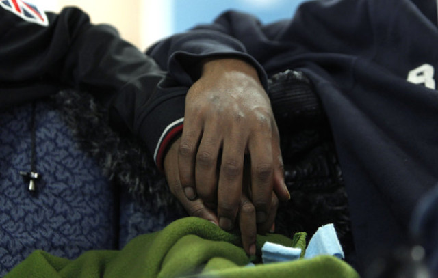 Two boys hold hands at the Ruth Ellis Center in Detroit, the only nonprofit agency in the Midwest that focuses on LGBT youths. It has 10 beds.  AP Photo by Paul Sancy, 2012.
