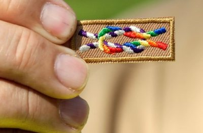 Image: A member of Scouts for Equality holds an unofficial knot patch incorporating the colors of the rainbow, a symbol for gay rights.