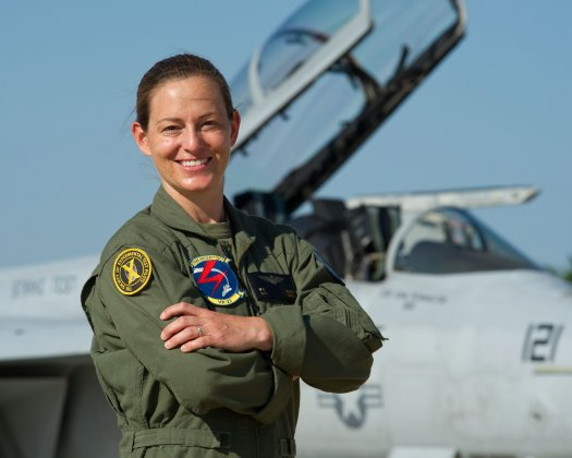 Nicole Aunapu Mann stands in front of an F-18, the twin-engine supersonic, all-weather carrier-capable multirole fighter jet she piloted for the Marines. Via PopSci.