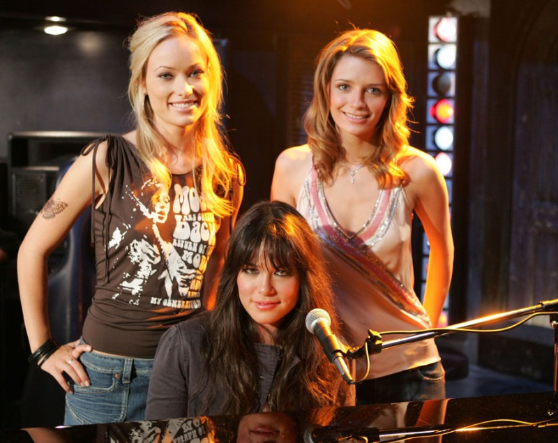 Image: Alex and Marissa are standing behind someone who i think might be famous who is sitting at a piano. Alex (Olivia Wilde) is wearing a sleeveless band t-shirt and Marissa's wearing a sparkly tank situation. It's a publicity photo so forced smiles all around.