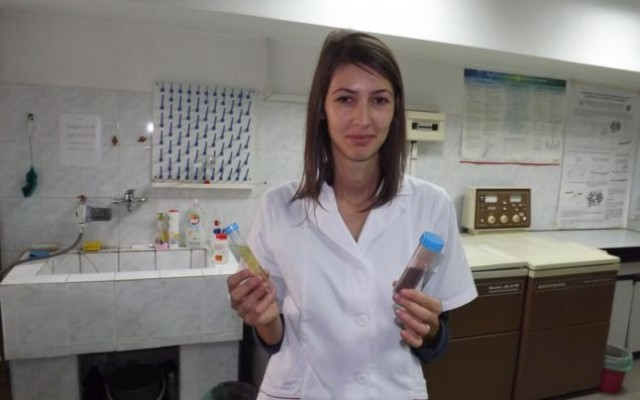 A woman holds two vials of fluid, one red, one yellow.