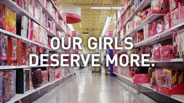 "A pink toy aisle with the words ""Our Girls Deserve More"" over top."