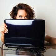 One eye on the screen, one eye on the bedroom door. via Shutterstock
