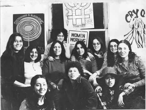 Members of the Chicago Women's Graphics Collective posing in front of signs they made in their print shop. The Collective