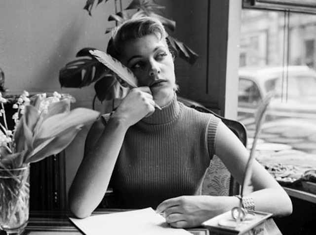 The only thing hotter than an attractive lady writing in her journal is an attractive lady writing in her journal while wearing a sleeveless mock turtleneck. (Via Planet Ivy)