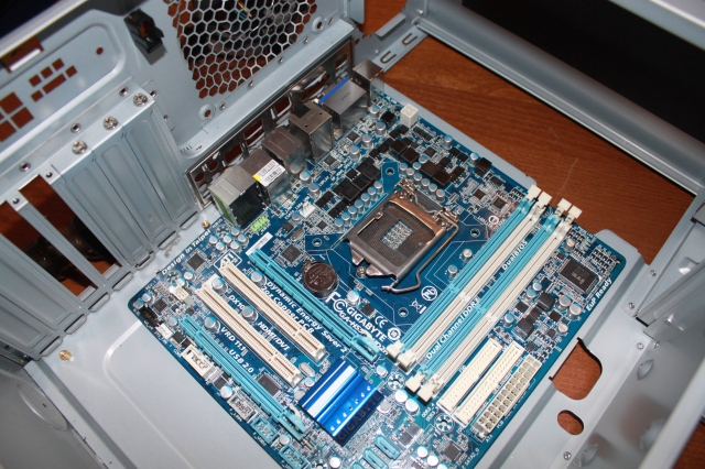 Line up the motherboard against the inside of the holes.