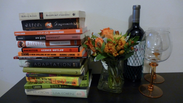 Stack of books next to a matching flower arrangement, a bottle of wine, and two wine glasses.