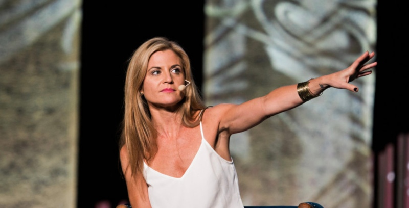 Glennon Doyle in a white tank top speaking on a stage