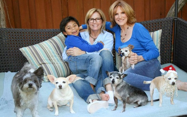 Leifer's son Bruno, her partner Lori Wolf and Carol Leifer herself with their eight rescue dogs, via life after 50