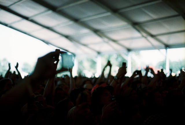 Several humans being excited under a tent.