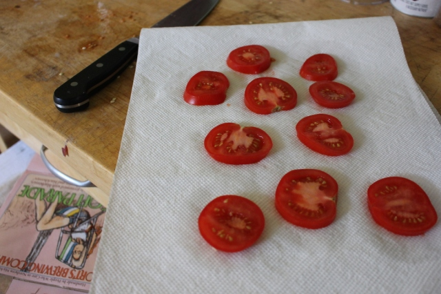 Setting tomatoes on a paper towel to soak up their liquid so the quiche doesn't get soggy!