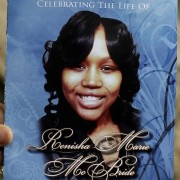 Image: A mourner holds an obituary showing a picture of shooting victim Renisha McBride during her funeral service in Detroit