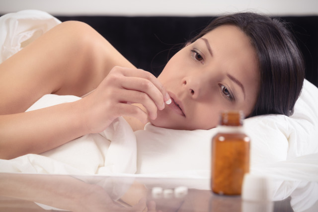 Woman looking at pill in bed.