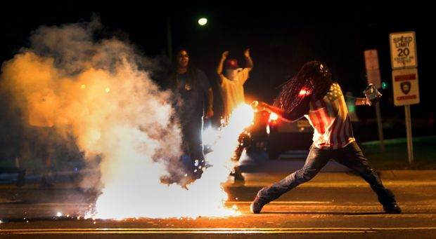 The now iconic photo of Edward Crawford throwing back a tear gas container after tactical officers worked to break up a group of bystanders. Photo by Robert Cohen, rcohen@post-dispatch.com. Via STLToday.