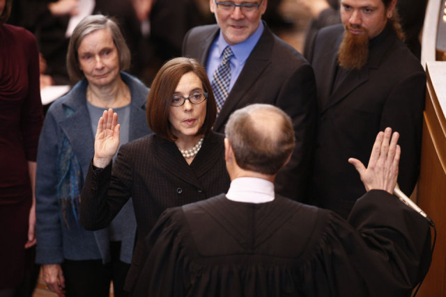 Chief Justice Thomas Balmer administers the oath of office to Secretary of State Kate Brown in the House chamber of the Oregon Capitol on Feb. 18, 2015. Brown becomes the state's 38th governor, succeeding John Kitzhaber, who resigned amid an ethics scandal. Bruce Ely/Staff