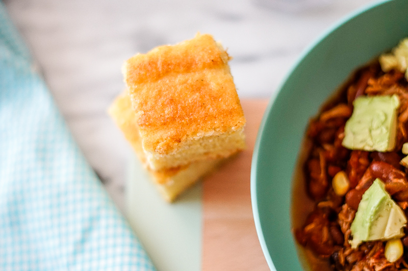 cornbread on a table next to a bowl of chili