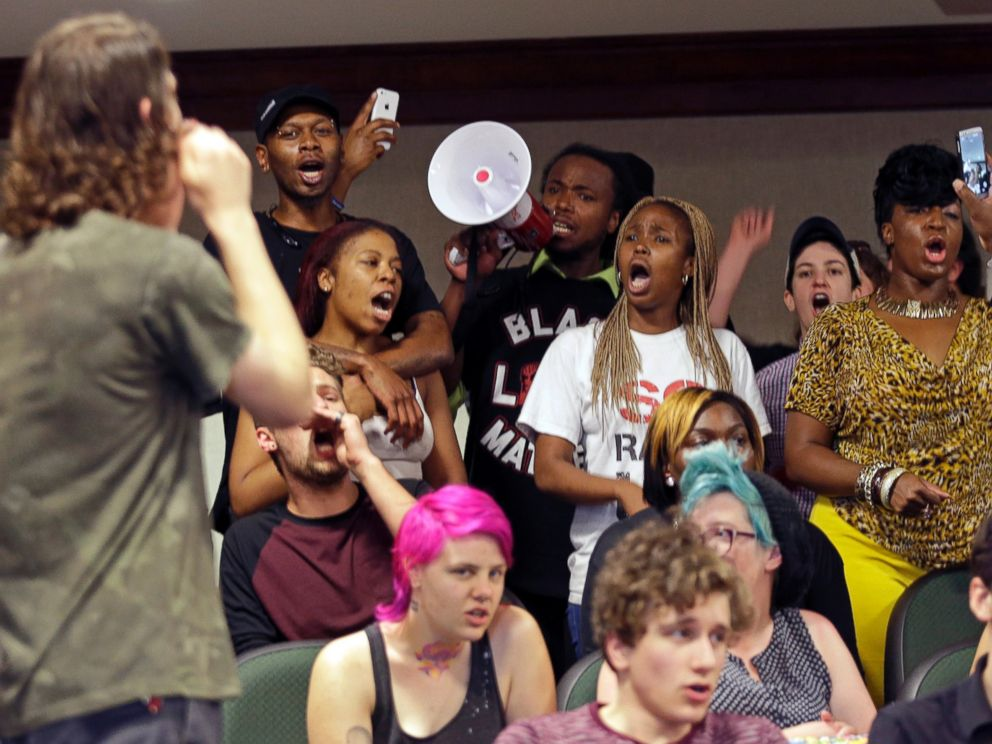 """Protesters shout during a news conference about the shooting death of Walter Scott at city hall in North Charleston, S.C., April 8, 2015."" by Chuck Burton / AP Photos"