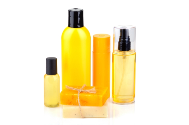 Several golden-colored bottles and bars of soap sit in a brightly lit field of white. These represent the most basic steps of a skincare routine.