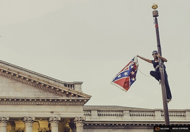 via Vox Bree Newsome triumphantly taking down the Confederate Flag