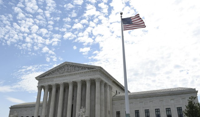 The flag flies in the wind in front of the Supreme Court in Washington, Monday, June 22, 2015. (AP Photo/Susan Walsh)