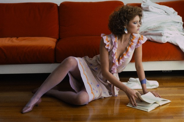 1981 --- Model Carrie Lowell seated on the floor with a red sofa behind her and an open book in her hands, wearing print wrap dress with ruffles by Zandra Rhodes, Cara Croninger purple bracelet, Hanes Ultra Sheer stockings, pink Vittorio Ricci shoes, and hair by John Sahag --- Image by © Condé Nast Archive/Corbis
