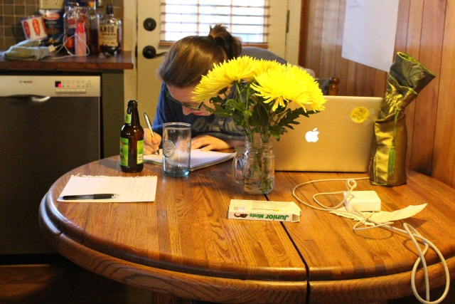 Heather is in her natural habitat, behind a vase of zinnias