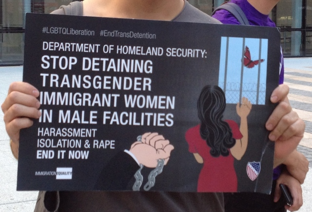 A protestor holds a sign outside ICE demanding an end to the detention of transgender immigrant women. photo by the author