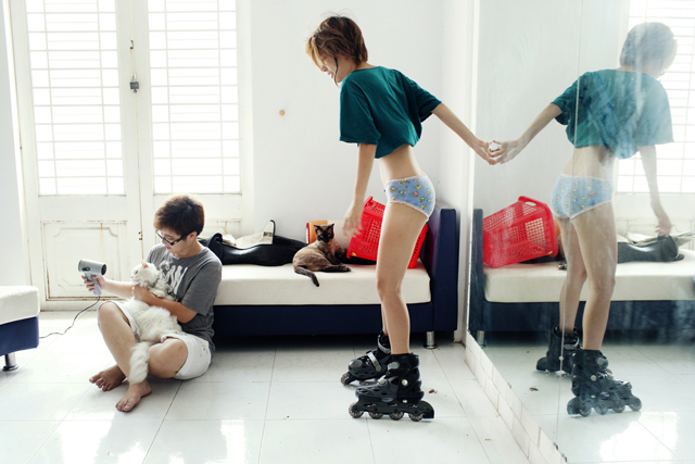 Phan Ngoc Hai Ly dries one of her cats after a bath while Pham Thao Huyen tries on new rollerblades