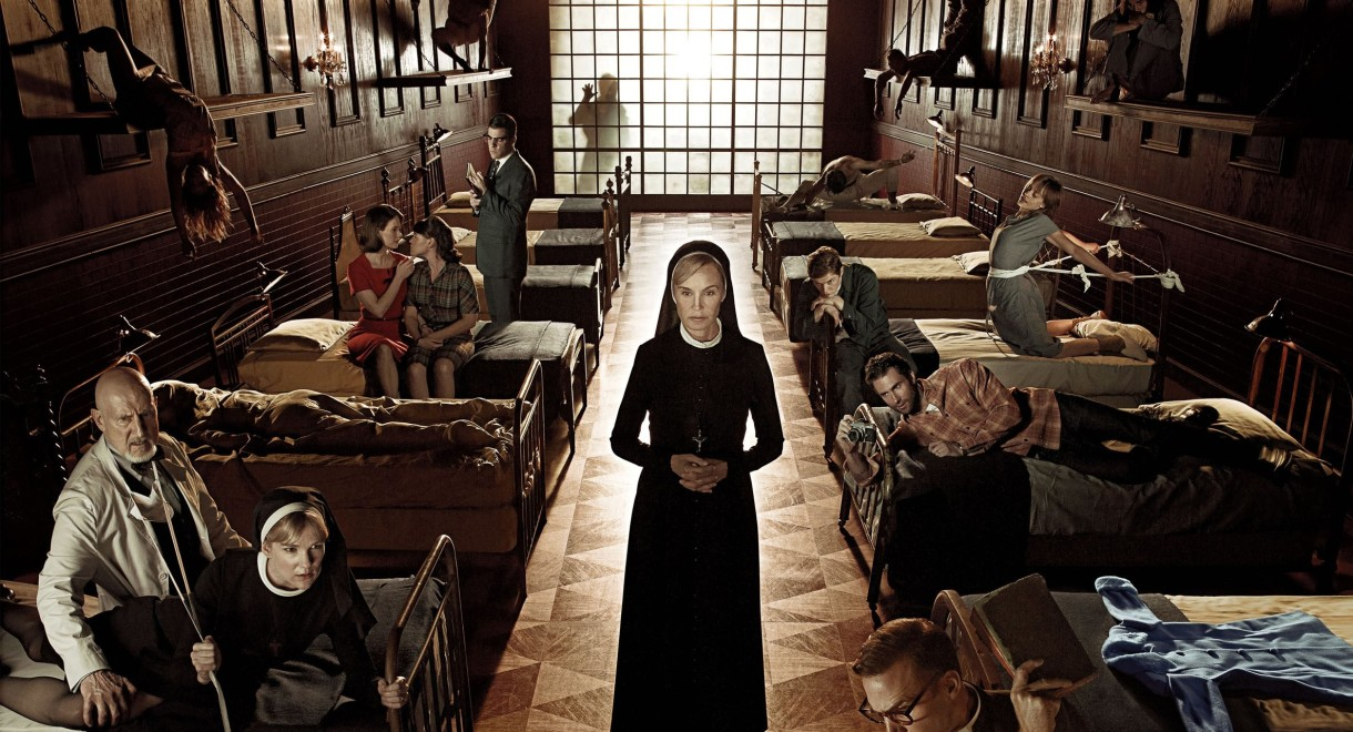 A nun (Jessica Lange) stands in the middle of an asylum bedroom, holding her hands together. Beds line both sides of the room, where various patients, doctors and nuns are captured in suspended actions.