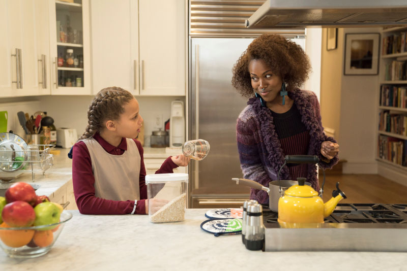 Image: Nola is in the kitchen with a younger girl, giving each other funny looks. The house looks expensive. They have a cute yellow teapot on the stove. The girl is holding a measuring cup and wearing what might be a school uniform.