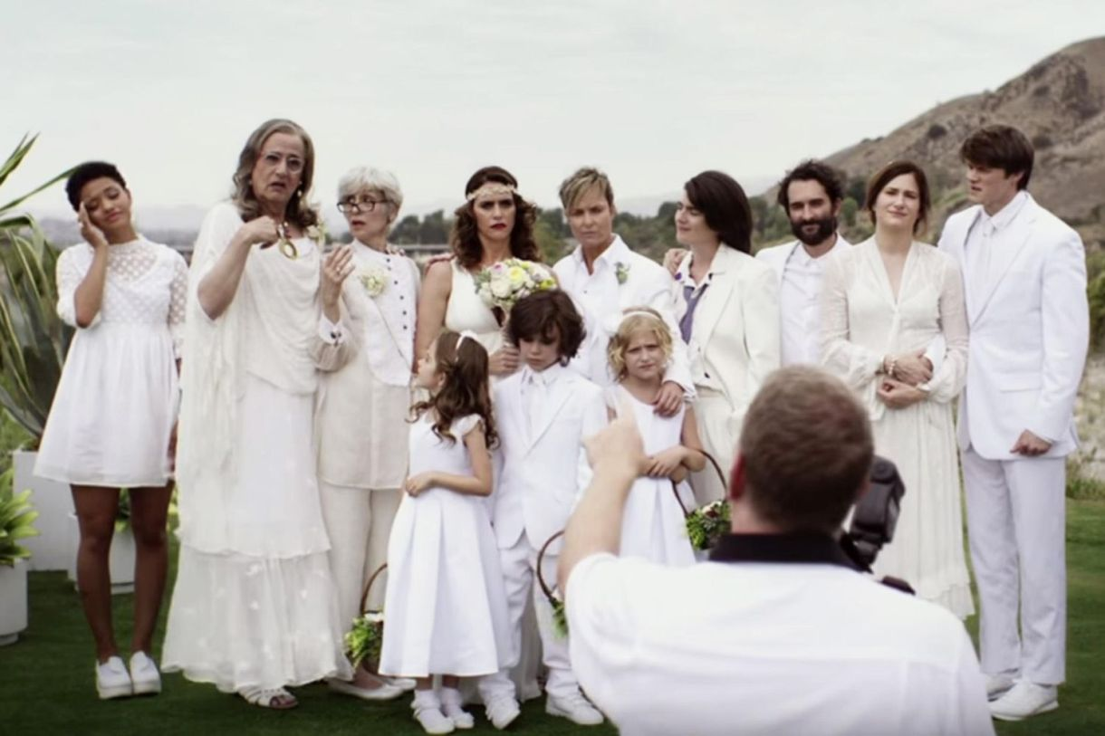 It is the lesbian wedding of Tami and Sarah Pfefferman. The entire Pfefferman family is dressed in white and standing on a green area close to beaches and mountains. A photographer is attempting to photograph the entire family. The wedding party also includes the rabbi and Josh's son.