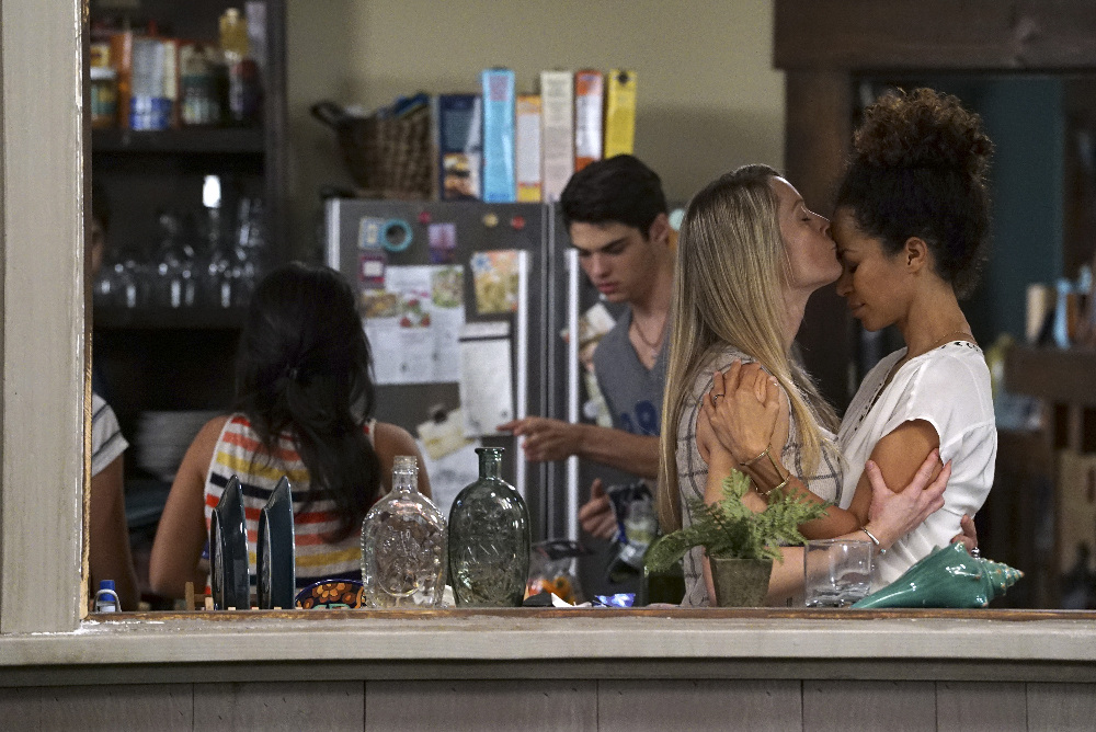 Image: Stef and Lena Foster are in the kitchen with two of their children. In the foreground, Stef and Lena are holding each other and Stef is kissing Lena on the forehead. In the background, their son is walking past the refrigerator, which has cereal boxes on top of it.