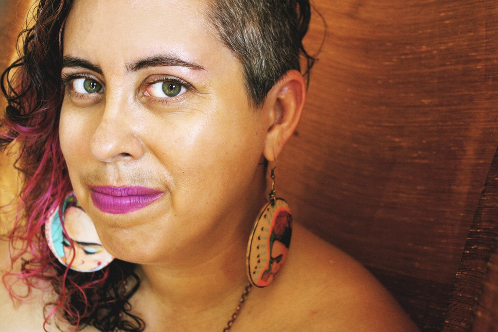 A woman with light brown skin, salt and pepper hair, and bright pink lips looks into the camera against a brown background. She is wearing large circular earrings featuring renderings of Frida Kahlo in either ear.