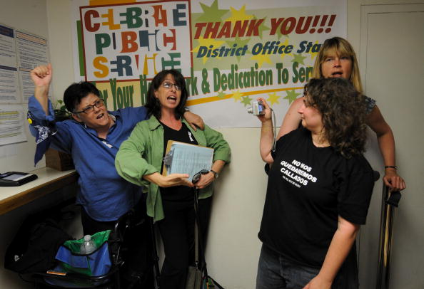 LOS ANGELES, CA - MAY 26: Susan Forrest (R) takes a snapshot of Jeanne Cordova (L) and Lynn Ballen (2L), as Forrest's partner Talia Betther looks on, as they lead a chant for demonstrators outside the East Los Angeles Marriage License Office May 26, 2009 in Los Angeles, California. They were part of a group that tried to obtain a marriage license after a rally, organized by Latino Equality Alliance, protesting the California Supreme Court ruling that upheld Proposition 8. The California Supreme Court upheld Proposition 8, a voter-approved ban on same-sex marriage, but also ruled that the estimated 18,000 gay couples who were marred in the state before the law took effect will stay wed. (Photo by Robert Hanashiro-Pool/Getty Images)