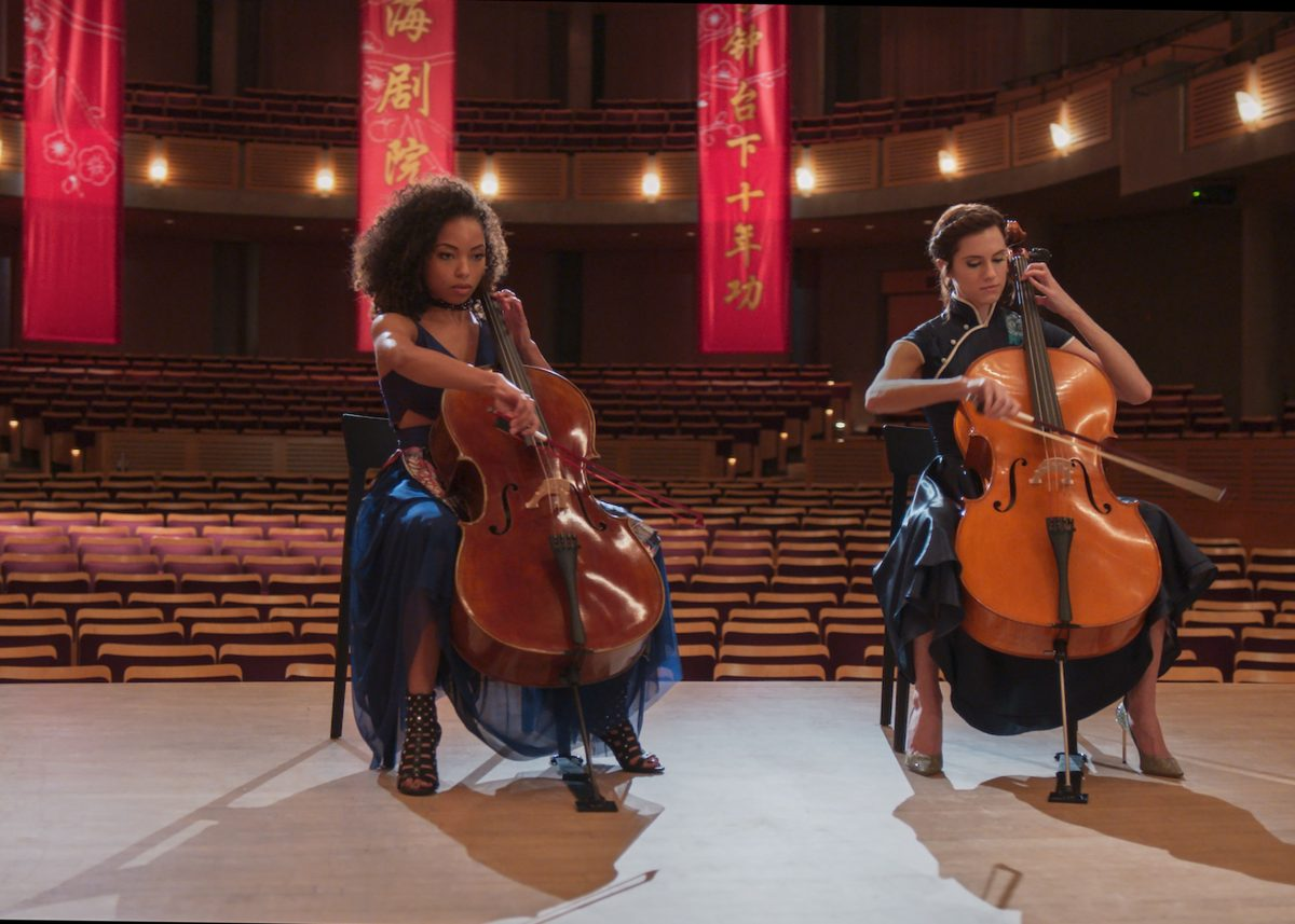 Two women playing cellos in an empty auditorium