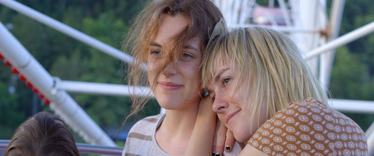 Two girls on a ferris wheel looking wistful