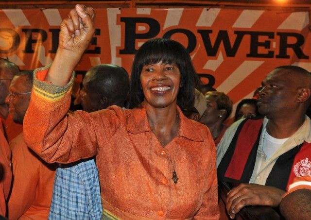 Portia Simpson Miller, leader of the People's National Party, pumps her fist to supporters during the victory rally of the parliamentary elections in Kingston, Jamaica, late Thursday, Dec. 29, 2011. Jamaica's opposition capitalized on discontent over the economy to return to power Thursday, defeating the center-right government of Prime Minister Andrew Holness, as voters gave the country's first female leader a second chance to govern the island. (AP Photo/Collin Reid)