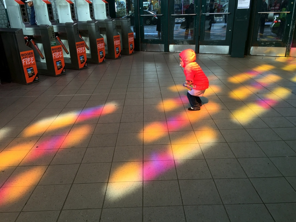 The subway station near my apartment has pink and yellow windows, and around 11am the sun is in the perfect spot to create these colors on the floor. As i was photographing them, the child in the photo started hopping around the colors. Their mother allowed me to use the photo, and the little one told me she though it was a cool photo.