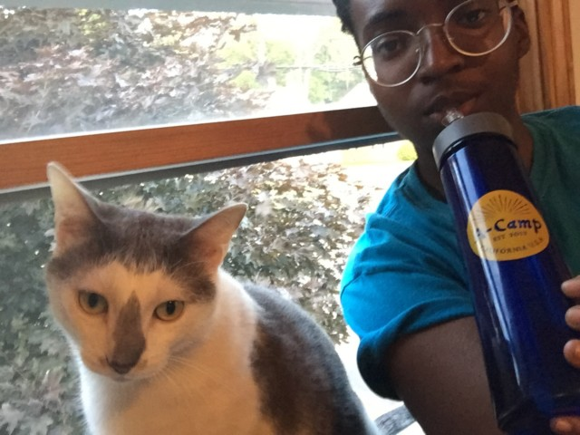 Alaina drinking from her A-Camp water bottle with her cat Alexei.
