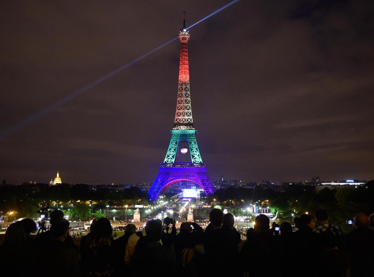 The Eiffel Tower in Paris, France, shines in the colors of a rainbow to honor victims of Sunday's mass shooting at an Orlando gay club, Monday, June 13, 2016. People brought banners, flags and candles to the Place Trocadero in front of the Paris landmark. (AP Photo/Martin Meissner)