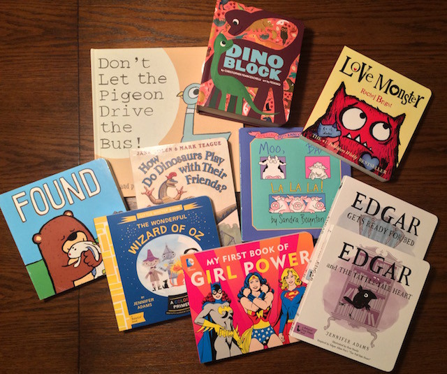 "A small sample from Remi's badass baby library: Don't Let the Pigeon Drive the Bus! by Mo Willems, Dino Block by Christopher Franceschelli, Love Monster by Rachel Bright, Found by Salina Yoon, How Do Dinosaurs Play With Their Friends by Jane Yolen, Moo Baa La La La by Sandra Boynton (my childhood favorite), The Wonderful Wizard of Oz: A BabyLit® Colors Primer by Jennifer Adams, My First Book of Girl Power by Julie Merberg, Edgar Gets Ready for Bed: A BabyLit® Board Book: Inspired by Edgar Allan Poe's ""The Raven"" by Jennifer Adams, and Edgar and the Tattle-tale Heart: A BabyLit® Board Book: Inspired by Edgar Allan Poe's ""The Tell-Tale Heart"" by Jennifer Adams"
