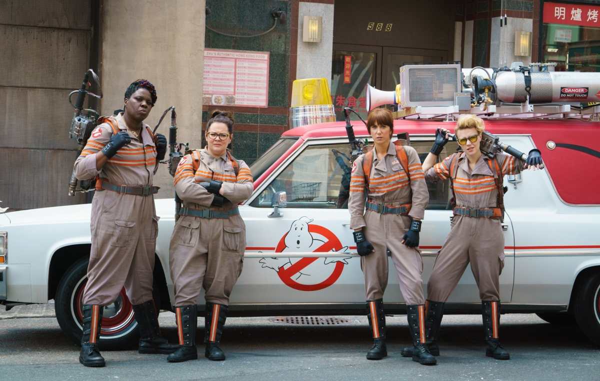 The ladies of Ghostbusters in front of their Ghostbusters car