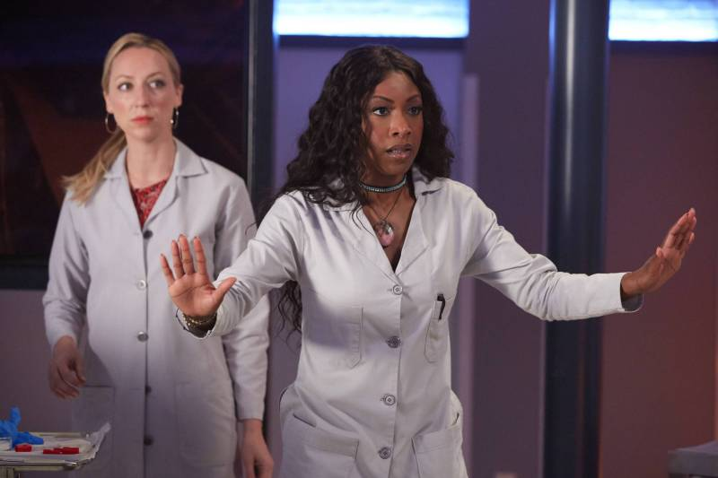 Image: two women in labcoats, one is white with long blonde hair and in the back, the other is Black and has her hands out like she's asking someone to stop