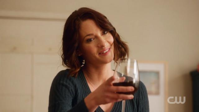 Alex holds a wine glass