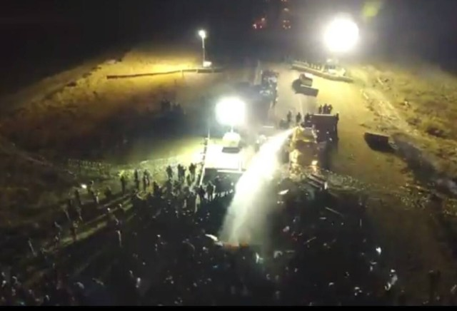 Drone footage of police using a water cannon on protestors while the temp hovered around 25° F.