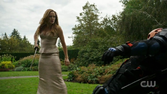 Sara in fighting stance and a bridesmaids dress
